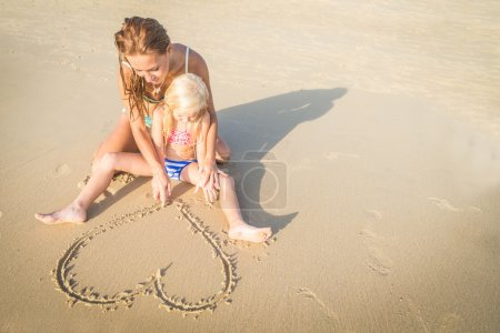 Photo for Young beautiful mom drawing a heart shape on the sand with her pretty daughter - Family on vacation playing on the beach - Royalty Free Image