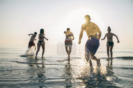 Photo for Group of happy friends running in to water at sunset - Silhouettes of active people having fun on the beach on vacation - Tourists going to swim on a tropical island - Royalty Free Image