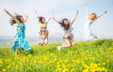 Photo for Four girls jumping in the nature. concept about airiness and carefree. - Royalty Free Image