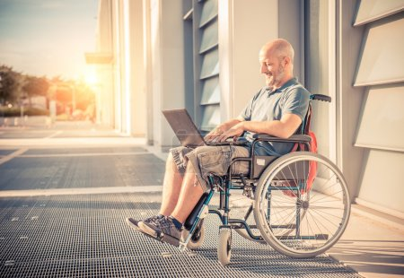 Photo for Disabled man on the wheelchair working with laptop computer outdoors - Handicapped senior man outside the hospital relaxing at sunset - Royalty Free Image