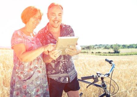 Photo pour Couple âgé regardant quelque chose sur la tablette. heureux sourire couple aîné avec tablette et vélo dans la nature - image libre de droit