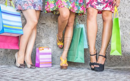 close up of three women with shopping bags, floor view with high heels and shopping bags