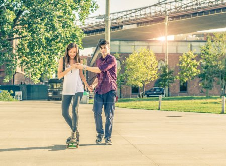 Photo for Young playful couple having a romantic date outdoors - Sportive man teaching her girlfriend to skateboarding - Teen lovers spending time together and having fun - Royalty Free Image