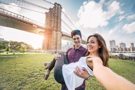 Photo pour Young pretty couple taking a selfie at Brooklyn Bridge, New York - Boyfriend holding his girlfriend and having fun while sightseeing - image libre de droit
