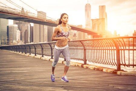 Photo pour Belle femme asiatique en cours d'exécution à New York au coucher du soleil. Pont de Brooklyn et horizon de Manhattan en arrière-plan - image libre de droit