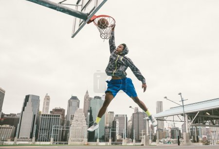 Basketball player performing slum dunk