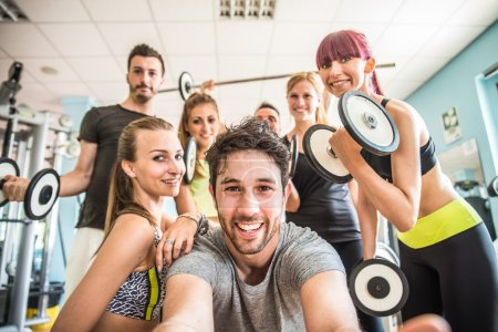 Photo for Group of sportive people in a gym taking selfie - Happy sporty friends in a weight room while training - Concepts about lifestyle and sport in a fitness club - Royalty Free Image