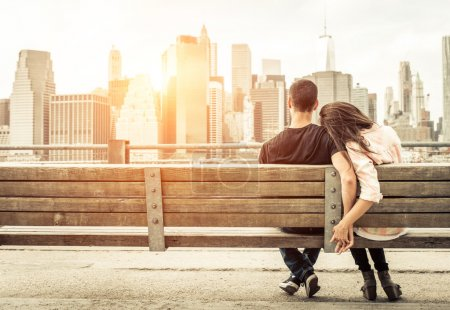 Photo for Couple relaxing on New york bench in front of the skyline at sunset time. concept about love,relationship, and travel - Royalty Free Image