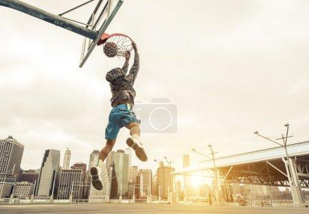 Photo pour Basketteur rue faisant un arrière de slam dunk. Bâtiments de New york et Manhattan en arrière-plan - image libre de droit