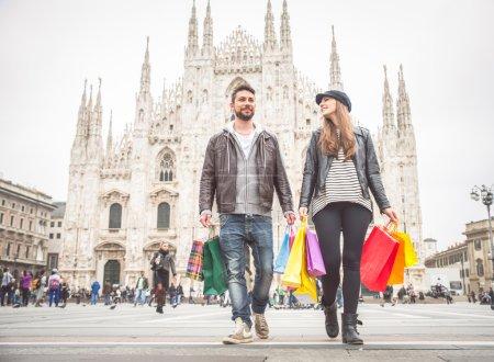 Photo pour Couple achetant des cadeaux lors d'une vente - Homme et femme attrayant tenant des sacs à provisions et s'amusant - humeur automne et hiver - image libre de droit