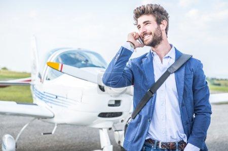 Photo pour Homme d'affaires avec ses avions. Il est à pied dans l'aéroport avec le téléphone intelligent et faire un appel. - image libre de droit