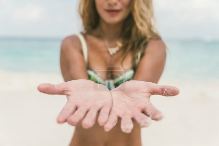 Woman on the beach with open hands showing palms