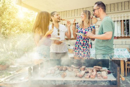 Photo for Group of friend having lunch in the backyard. making barbecue outdoor with differnt kind of meat and vegetables - Royalty Free Image