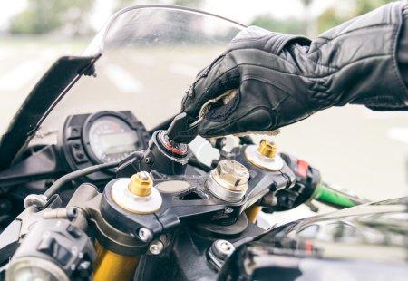 Photo pour Action d'allumage moto. Insérer la clé et démarrage du moteur pilote - image libre de droit
