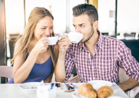 Photo for Happy couple in a coffee house having breakfast - Pretty lovers in a restaurant looking each others in the eyes - Royalty Free Image
