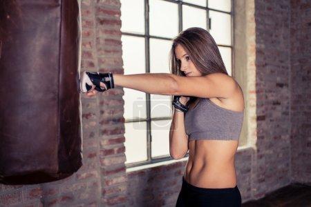Photo pour Chasseur femme formation au sac lourd. formation le poinçon Croix - image libre de droit