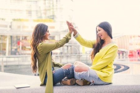 Foto de Dos hermosas mujeres jóvenes dando cinco alta - chicas guapas sentadas en un banco al aire libre y divertirse - mejores amigas haciendo una promesa - Imagen libre de derechos