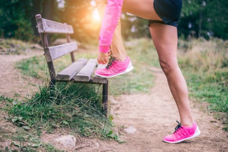 Photo for Woman tying shoelaces before start running - Sportive girl jogging in a park , close up on running shoes - Concepts about sport and lifestyle - Royalty Free Image
