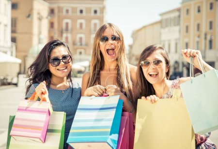 Three happy girls having fun and making shopping