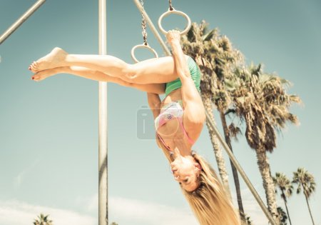 Blonde girl making gymnastic in the park