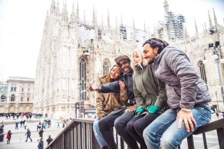 Multiracial group of friends taking selfie in Milan