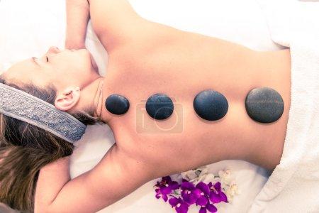 Woman having massage with hot stones