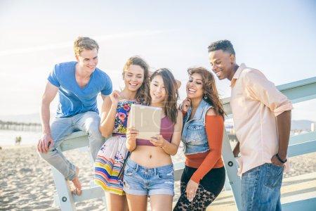 Photo pour Groupe multi-ethnique d'amis regarder la tablette sur la plage - cinq personnes des divers groupes ethniques s'amuser avec la technologie moderne - image libre de droit