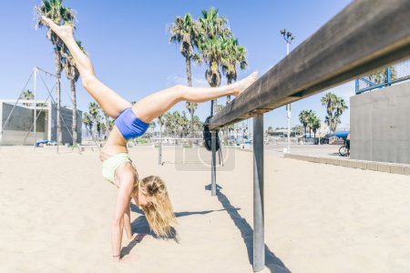 Photo for Woman doing stretching exercise on the beach - Sportive girl working out - Royalty Free Image