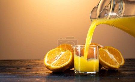 Du jus d'orange éclaboussé sur le verre. ext à elle sur la table sont tranchés et des oranges entières. le soleil couchant. fond orange
