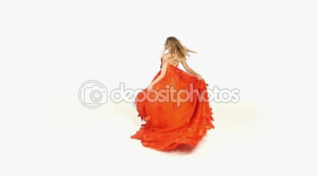 Beautiful girl in gorgeous red dress whirling, isolated on white,  slow motion
