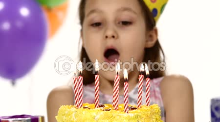 Birthday girl blows out  candles on a birthday cake. In the background, balls. Slow motion