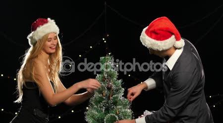 Friends in Santa caps decorate Christmas tree, on black, bokeh