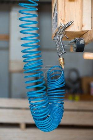 Photo pour Flexible à air pneumatique comprimé bleu avec pistolet accroché à vis - image libre de droit