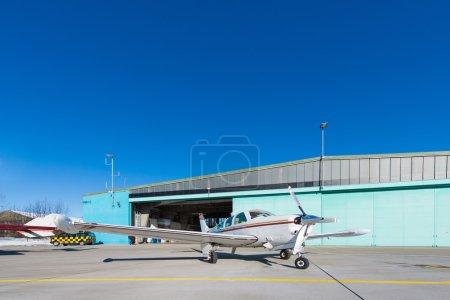 Small aeroplane standing before aircraft hangar at blue sky