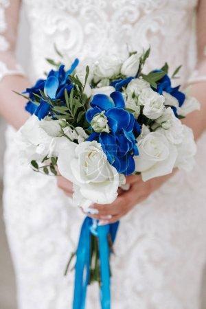 Photo pour Bouquet de mariage de roses blanches et de fleurs bleues dans la main de la mariée lors de la cérémonie, rubans bleus. Décoration florale à un mariage. Contexte pour les célébrations de mariage - image libre de droit