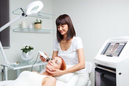 Photo pour Photo de jolie esthéticienne faisant la procédure rf-levage pour jeune femme fixant dans un salon de beauté - image libre de droit