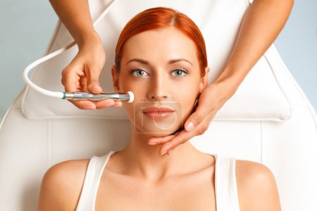 Photo pour Closeup portrait of lovely redheaded woman getting microdermabrasion procedure in a beauty salon - image libre de droit