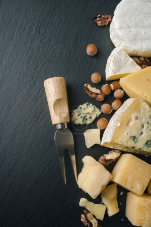 Photo for Different varieties of cheese and nuts on a black board - Royalty Free Image