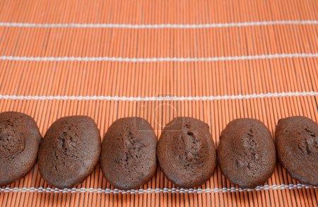 Eine Reihe hausgemachter Bio-Schokolade Madeleines auf einem rot-orangen Bambus-Tischset. Kopierraum.