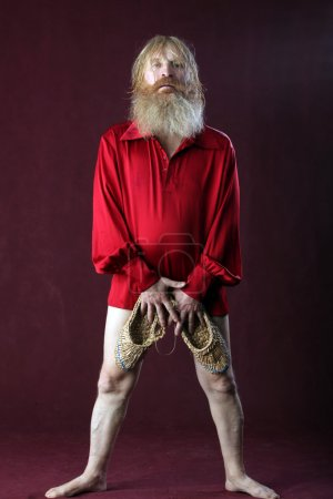 Photo pour Verticale d'un homme dans une chemise rouge avec la barbe longue de cheveux et la moustache avec un bâton et des chaussures de bast dans le studio de mains sur un fond bordeaux - image libre de droit