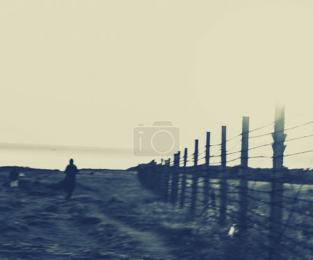 person walking along fence with barbed wire
