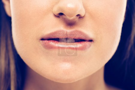 Photo for Cropped image of beautiful female face biting lips - Royalty Free Image