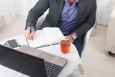 Podnikatel v kanceláři sedí u stolu s notebookem píše s koncentrací