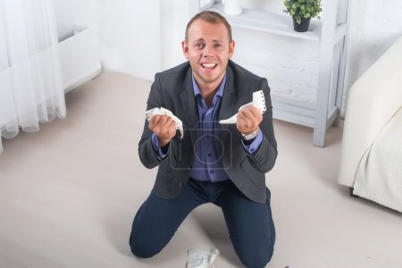 Young male businessman anger, hysterical kneeling on the floor, screaming and holding crumpled paper in his hands