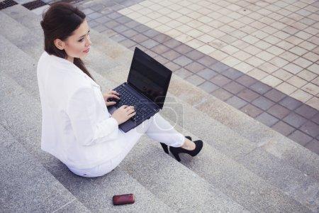 Photo pour Belle femme d'affaires brune en costume blanc avec ordinateur portable sur ses genoux, dactylographiant, travaillant à l'extérieur. Espace de copie - image libre de droit