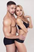 Sexy fit muscled couple in sportswear on neutral grey background