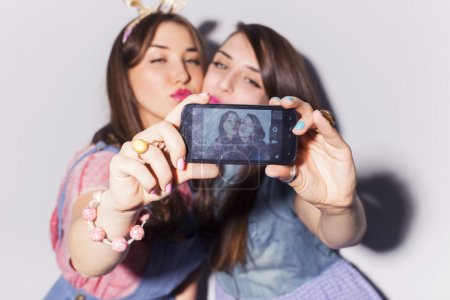 Two beautiful brunette women (girls) teenagers spend time togeth