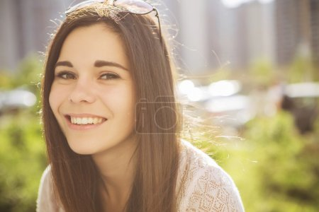 Photo for Beautiful brunette caucasian young woman laughting showing perfect teeth on summer sunny day. outdoors. nature. copy space - Royalty Free Image