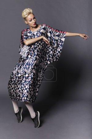 Photo pour Jeune modèle femme transgenre blonde en robe longue à motif bleu, collants blancs et baskets noires, avec maquillage créatif : lèvres rouges et sourcils rouges. Fond gris neutre. Studio - image libre de droit