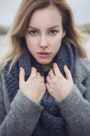 Beautiful blonde young caucasian woman in grey coat and scarf wa